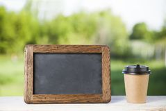 Coffee paper cup with chalk board, on wood table, summer day bac. Kground royalty free stock photos