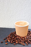 Coffee in a paper cup on a light background with coffee beans around Stock Image