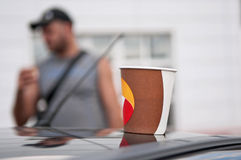 Coffee in a paper cup on the roof of the car closeup Stock Photos