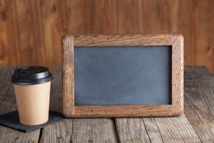 Coffee paper cup with vintage slate chalk board, on grunge wood. Table Royalty Free Stock Photo