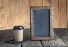Coffee paper cup with vintage slate chalk board, on grunge wood. Table Stock Photography