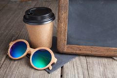 Coffee paper cup with vintage slate chalk board, on grunge wood. Table, and sun glasses Royalty Free Stock Photos