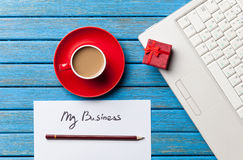 Coffee and paper with My Business inscription near notebook Stock Image