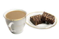 Coffee and pastries. Coffee in a cup next to delisious chocolate square pastries on a saucer. Cup and saucer both have matching golden edges. Clipping path Royalty Free Stock Photography