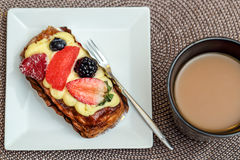 Coffee and pastry. A mug of coffee and fruit pastry on a white plate with a little fork Stock Photography