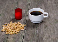 Coffee, peanut and red candle, on a wooden table Royalty Free Stock Photography