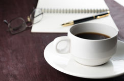 Coffee pen and book on wooden table Royalty Free Stock Images