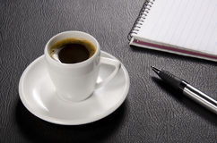 Coffee, pen and pad. On a black leather texture. Beautifully lit and composed Royalty Free Stock Images