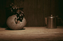 Coffee percolator, black grapes on wooden table, copy space. Royalty Free Stock Photo