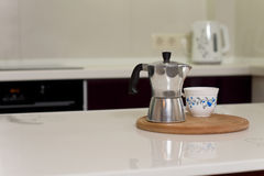 Coffee percolator and cup on a kitchen counter Royalty Free Stock Images