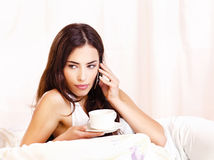 Coffee and phone in bed Royalty Free Stock Image