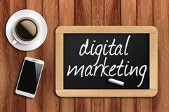 Coffee, phone and chalkboard with digital marketing words Stock Photos