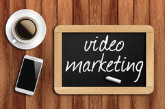 Coffee, phone and chalkboard with video marketing words Stock Photo