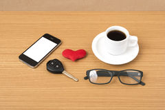 Coffee,phone,eyeglasses and car key. On wood table background Stock Photo
