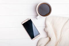 Coffee, phone and knitted sweater on the white table. Top view Royalty Free Stock Images