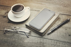 Coffee, phone, notebook, pen and glass. Cup of coffee, smart phone on notebook, pen and glass Royalty Free Stock Images
