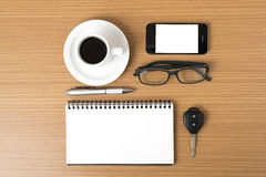 Coffee,phone,notepad,eyeglasses and car key. On wood table background Stock Photo