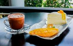 Coffee with a piece of mango cheese cake on table wooden Royalty Free Stock Photography