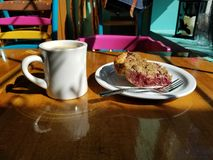 Coffee and a piece of strawberry pear rhubarb pie with colorful chairs and a bag in the background stock images