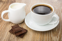 Coffee, pieces of chocolate and milk jug on table Stock Image