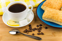 Coffee, pieces of lemon and sugar, plate with flaky biscuits Royalty Free Stock Photography