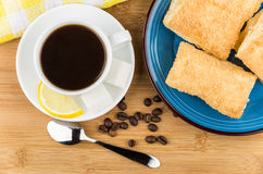 Coffee, pieces of lemon and sugar, plate with flaky biscuits Stock Photography