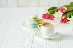 Coffee, pink and white tulips and macarons on the white wooden table Stock Photos