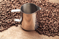 Coffee pitcher and beans on old wooden table Stock Photos