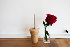 Coffee in plastic cup and artificial rose on wooden table Royalty Free Stock Image