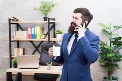 Coffee is pledge of successful negotiations. Caffeine addicted. Man bearded businessman hold cup and smartphone. Mobile. Call. Start day with coffee. Coffee royalty free stock photos