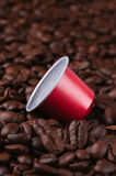 Coffee pod on a bed of coffee beans Royalty Free Stock Photos