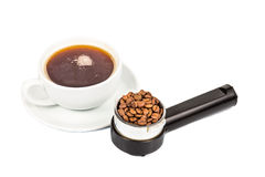 Coffee portafilter filled with coffee beans with a cup of freshly brewed espresso at the background Stock Photo