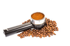 Coffee portafilter filled with finely grounded coffee, and with coffee beans scattered around Stock Images