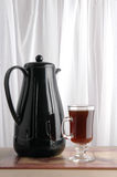 Coffee Pot. A pot and cup of coffee are on a table before a window Stock Photos