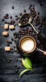 Coffee pot with coffee beans, cane sugar and fresh leaves. Stock Photography