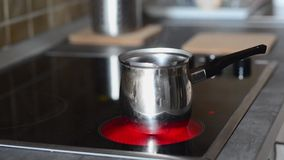 Coffee pot on cooking plate with boiling water in. Stock Photos