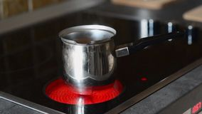 Coffee pot on cooking plate with boiling water in. Stock Photography