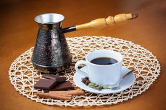 Coffee pot, cup of coffee, spices and pieces of chocolate Stock Photos