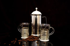 Coffee pot and cups. Coffee pot with cups and coffee beans isolated on black Stock Images