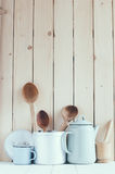 Coffee pot, enamel mugs and rustic spoons. Home kitchen still life: Vintage coffee pot, enamel mugs and antique rustic wooden spoons on a barn wall background stock photo