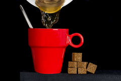 Coffee pot filling a red cup. With brown sugar cane cubes over a black background Royalty Free Stock Photography