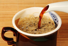 Coffee from the pot is poured into the cup. Royalty Free Stock Photos