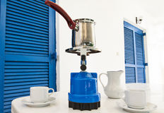 Coffee pot on a primus stove with cups on summer veranda. Royalty Free Stock Photo