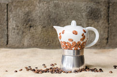 Coffee pot on rustic background. Ceramic coffee pot and coffee beans on a jute and a rustic background Royalty Free Stock Photos
