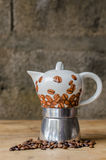 Coffee pot on rustic background. Ceramic coffee pot and coffee beans on a old wooden table and a rustic background Royalty Free Stock Photos