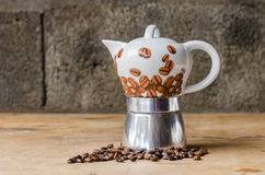 Coffee pot on rustic background. Ceramic coffee pot and coffee beans on a old wooden table and a rustic background Royalty Free Stock Image