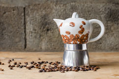 Coffee pot on rustic background. Ceramic coffee pot and coffee beans on a old wooden table and a rustic background Royalty Free Stock Photo