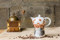 Coffee pot on rustic background. Ceramic coffee pot, vintage coffee grinder and coffee beans on a jute and a rustic background Stock Image