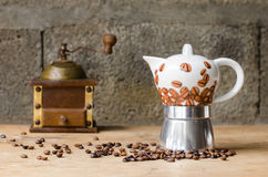 Coffee pot on rustic background. Ceramic coffee pot, vintage coffee grinder and coffee beans on a old wooden table and a rustic background Royalty Free Stock Photo