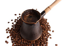 Coffee pot staying on the beans. On white background Royalty Free Stock Photography